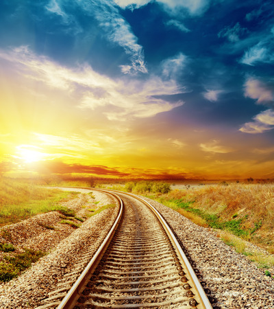 good sunset in colored sky over railroad photo