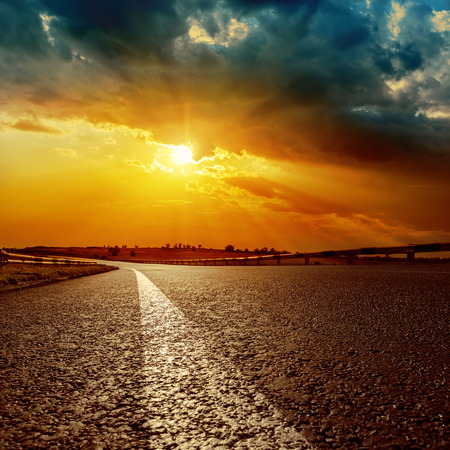 field sunset: dramatic sunset and white line on asphalt road to horizon