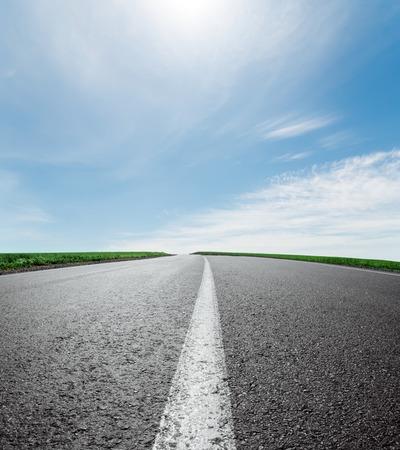 asphalt road to horizon under sky with clouds and sun Standard-Bild
