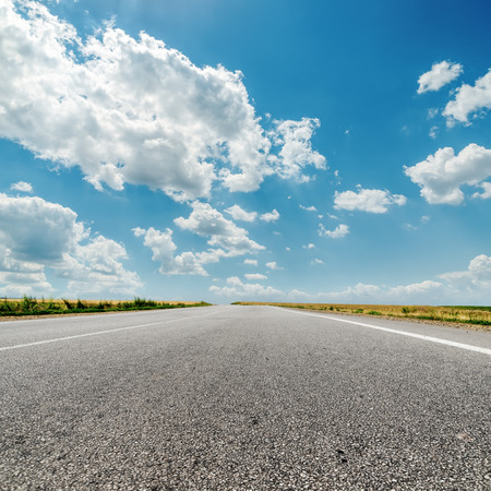 long road: asphalt road to horizon and clouds over it Stock Photo