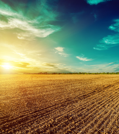 sunset in dramatic sky over plowed field 스톡 콘텐츠