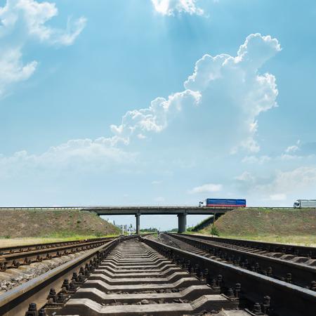 high powered: railway goes to horizon under bridge with autos Stock Photo