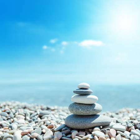 zen-like stones on beach and sun in sky. soft focus on bottom