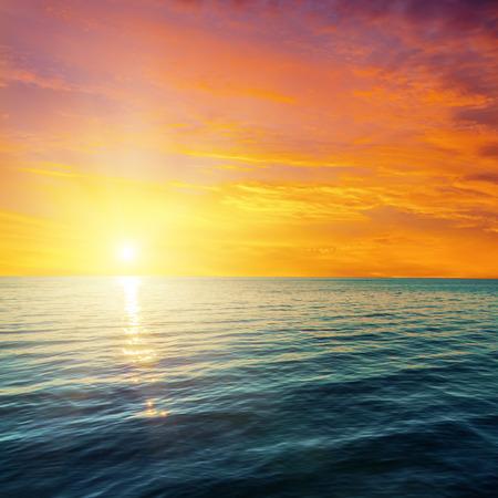 olas de mar: puesta de sol rojo sobre el mar oscuro Foto de archivo