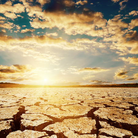 sky: dramatic sunset over drought earth Stock Photo