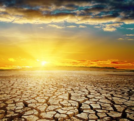 opwarming van de aarde. Dramatische zonsondergang over gebarsten aarde