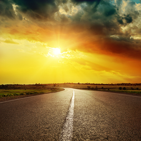 road travel: central white line on asphalt road and dramatic sunset