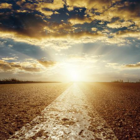 中央の白いラインとアスファルトの道路の上の低い雲に夕日