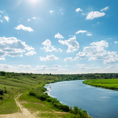 green river: sun in blue sky with clouds over river