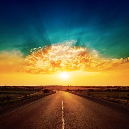 tramonto arancione e strada asfaltata fino all'orizzonte