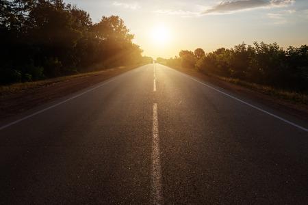 日没の地平線にアスファルトの道路 写真素材