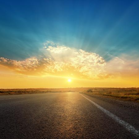 asfaltweg en zonsondergang in de wolken Stockfoto