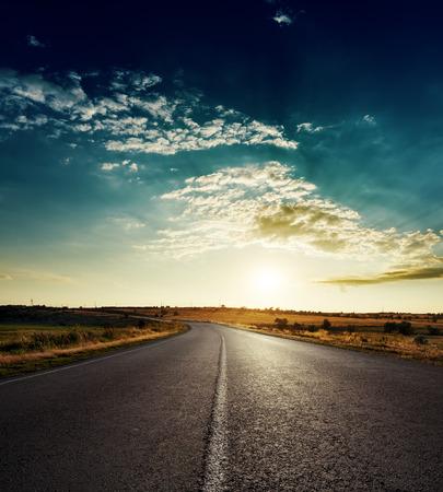 白い線のアスファルトの道路に沈む夕日