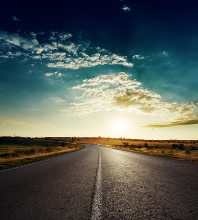dramatic sunrise: sunset over asphalt road with white line