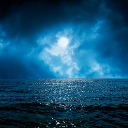 sea wave: moon light in dramatic sky over dark sea