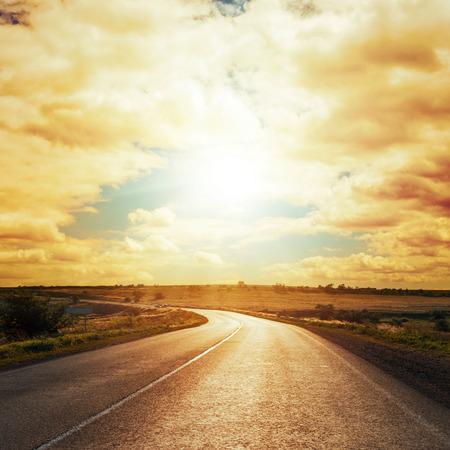 アスファルトの道路上の雲でドラマチックな日没