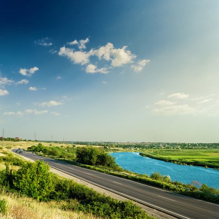 green lines: asphalt road and river under sunset in blue sky with clouds