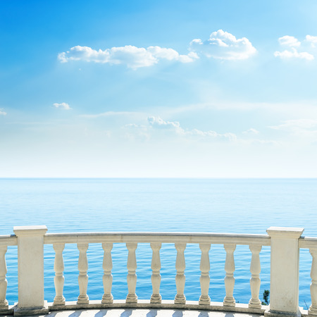 balcony view: white balcony on sea beach and clouds in sky