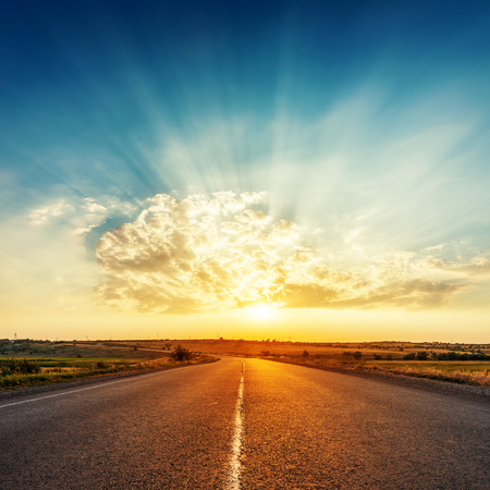 sunset in clouds with sunrays over road to horizon