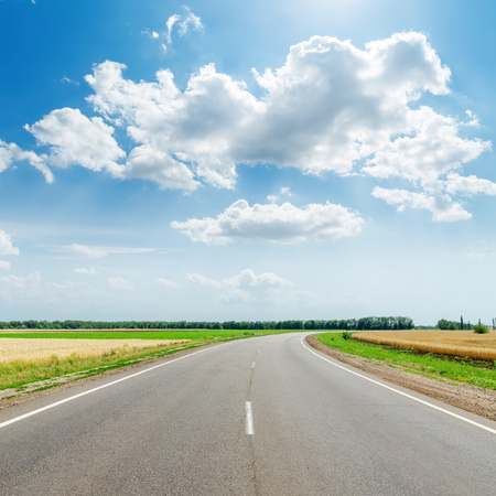 green road: asphalt road under clouds with sun