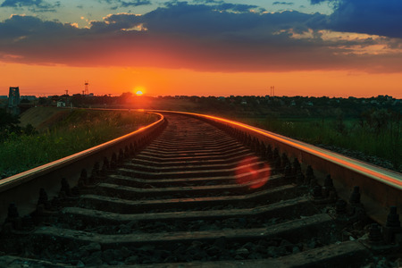 railway transportation: low red sun on sunset over railway