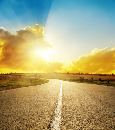 dramatic sunrise: bright sunset over road Stock Photo