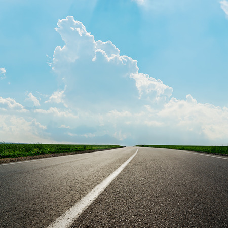 green road: asphalt road with white line and clouds in blue sky
