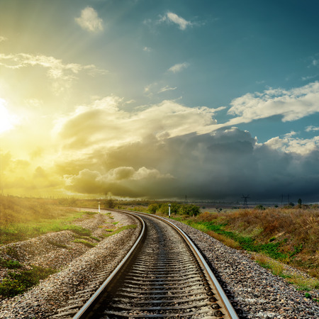 railroads: railroad to horizon and sunset in clouds Stock Photo