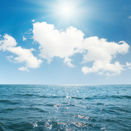 seascape: sun in blue sky with clouds over sea
