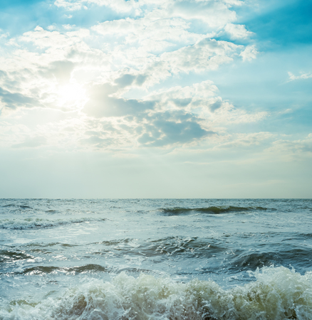 breaking wave: storm sea and dramatic sky with sun Stock Photo