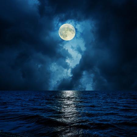 noche y luna: luna estupenda en nubes sobre el agua