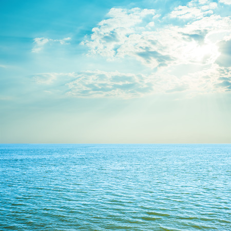 ocean water: blue sea and cloudy sky over it. sunset time Stock Photo