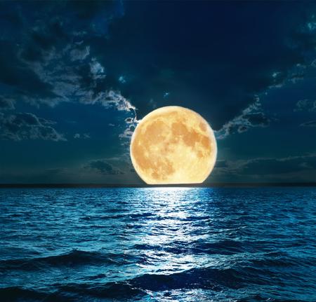 noche y luna: súper luna sobre el agua Foto de archivo