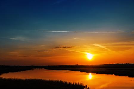 orange sunset: dark orange sunset over river Stock Photo