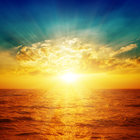 bright sunset in dramatic sky over sea Standard-Bild