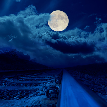 voyage: railroad closeup in night under full moon in clouds