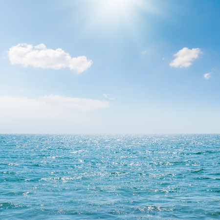 blue and white: sun in blue sky over sea Stock Photo