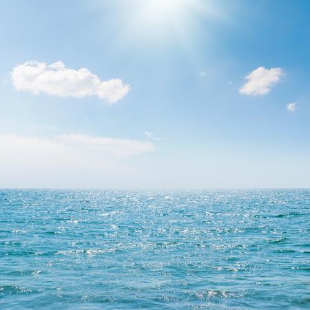 zon in blauwe hemel over zee
