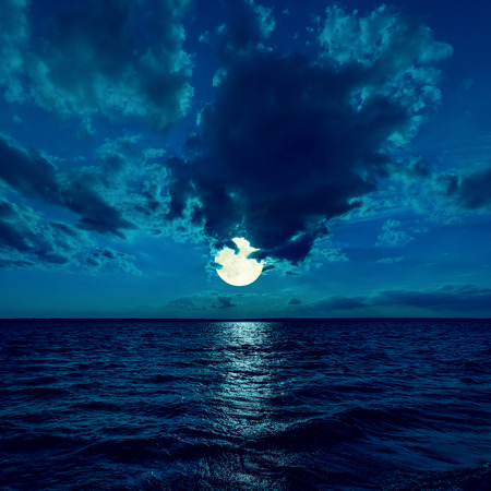 over the moon: full moon in dramatic sky over water in night