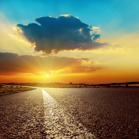 road vehicle: dark clouds over asphalt road on sunset