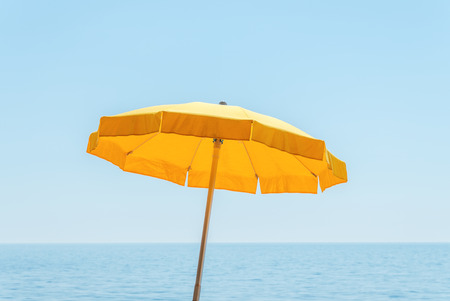 yellow umbrella: yellow umbrella near sea under blue sky