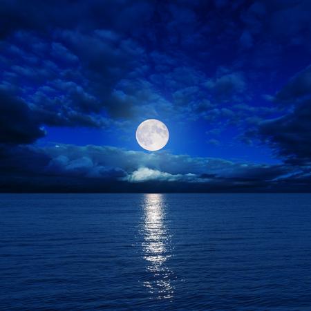 niedrige Mond in den Wolken über den Fluss