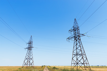 electric blue: two electric tower under blue sky Stock Photo