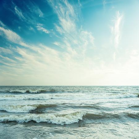 雲と夕日の嵐の海と青い空