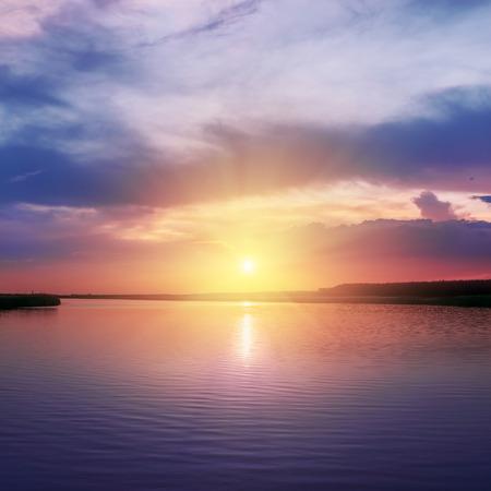 orange sunset: orange sunset over river in purple colors around Stock Photo