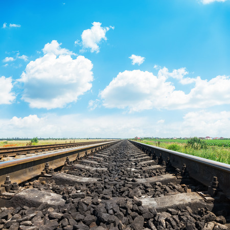 long way: railroad closeup to horizon and bright day with blue sky and white clouds
