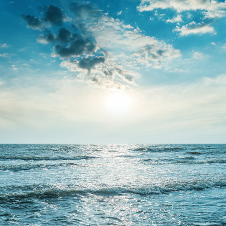 over the sea: low sun in blue sky over sea with wave