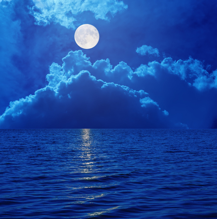 horizon over water: super moon in sky with clouds over sea