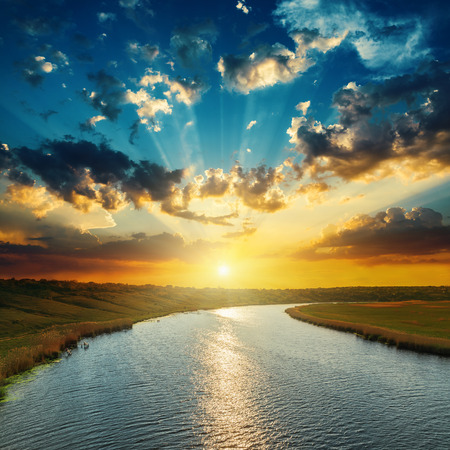 horizon over water: sunset with clouds, light rays over river with reflections Stock Photo
