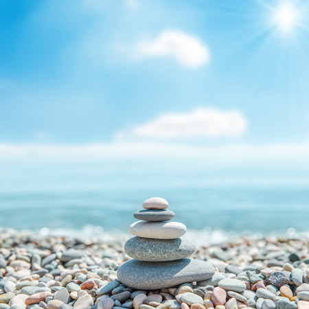 stack of zen stones near sea and clouds with sun on background